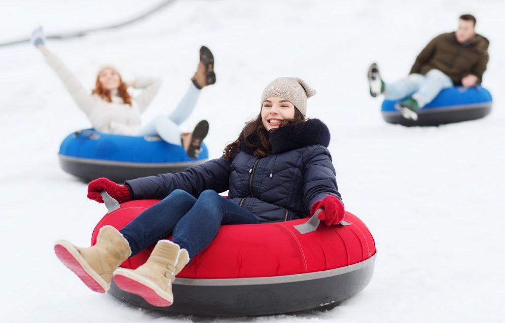 Friends sliding down on snow tubes