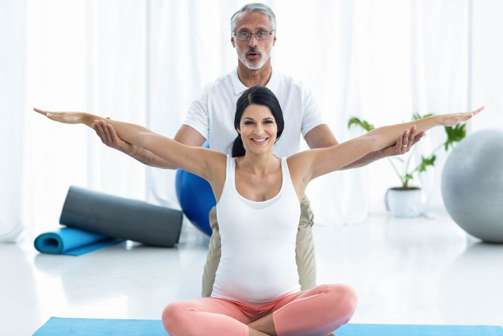 Pregnant woman being assisted by a fitness instructor