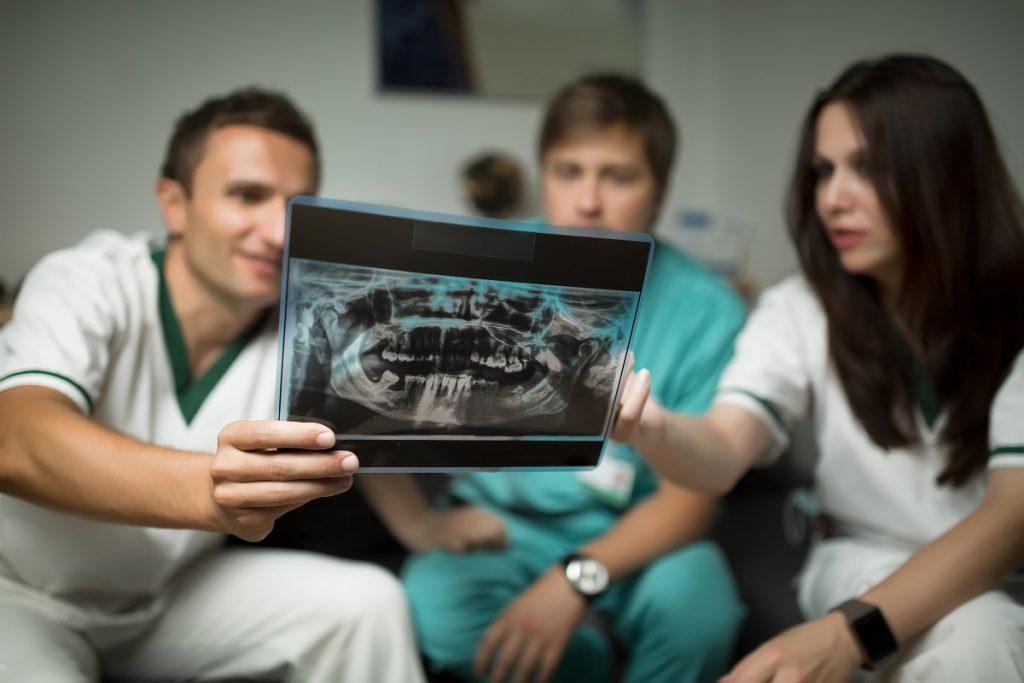 Dentists looking at teeth x-ray