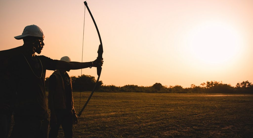 Man using a bow and arrow during sunset