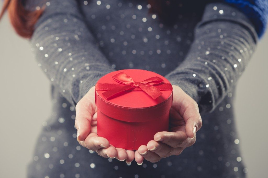 woman holding a small round gift box
