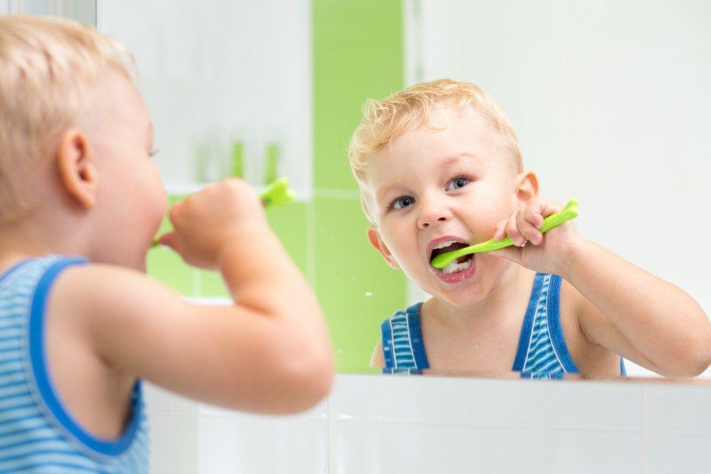 a kid brushing his teeth
