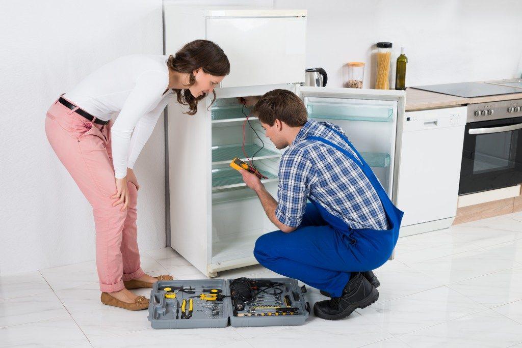 Male Worker Repairing Refrigerator In Kitchen Room