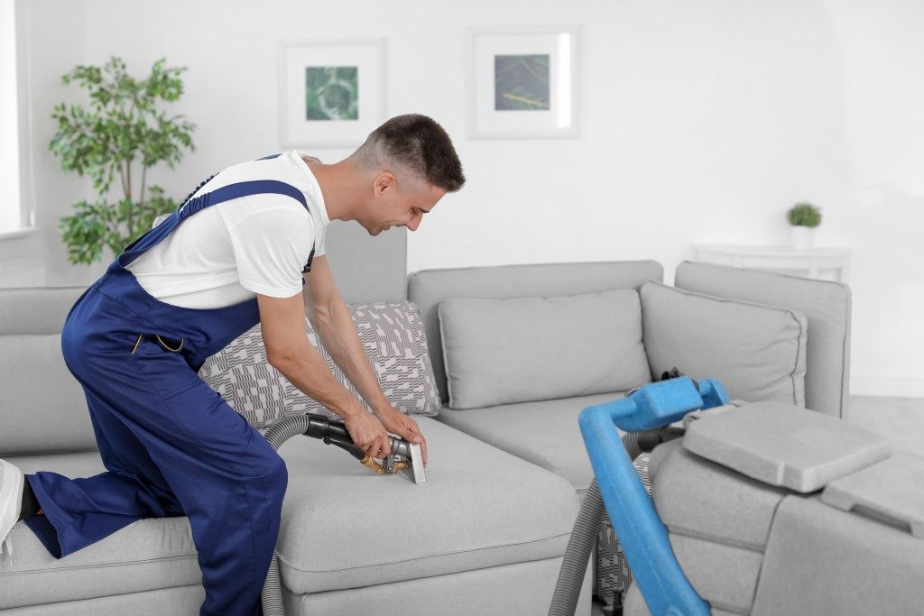 man cleaning the couch