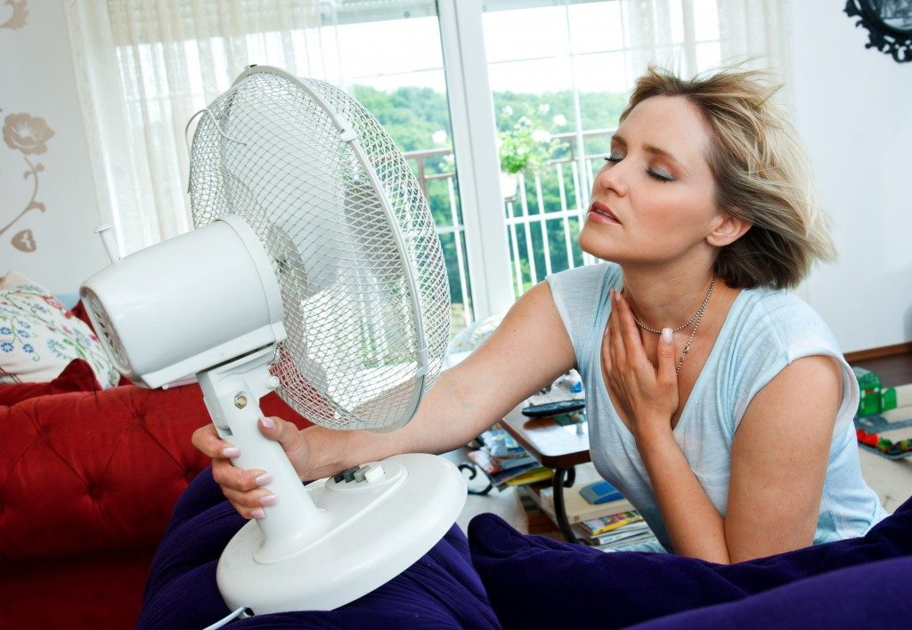 woman cooling herself with fan