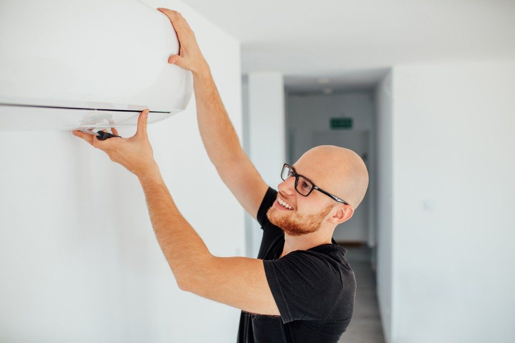 man adjusting some features in the air conditioning unit