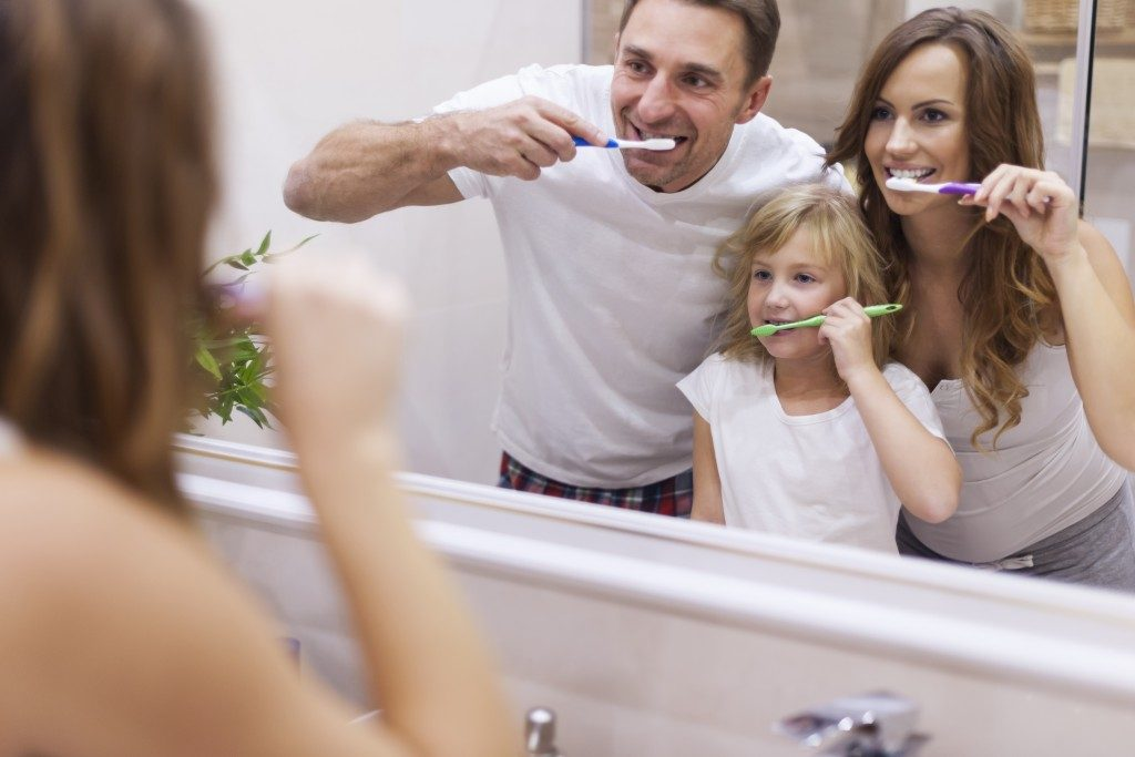 mom and dan brushing teeth with daughter