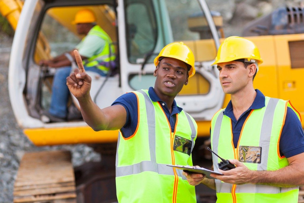 co-workers talking at construction site with bulldozer behind them