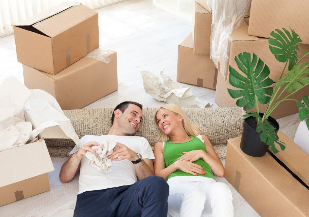smiling couple relaxing in the middle of cardboard boxes