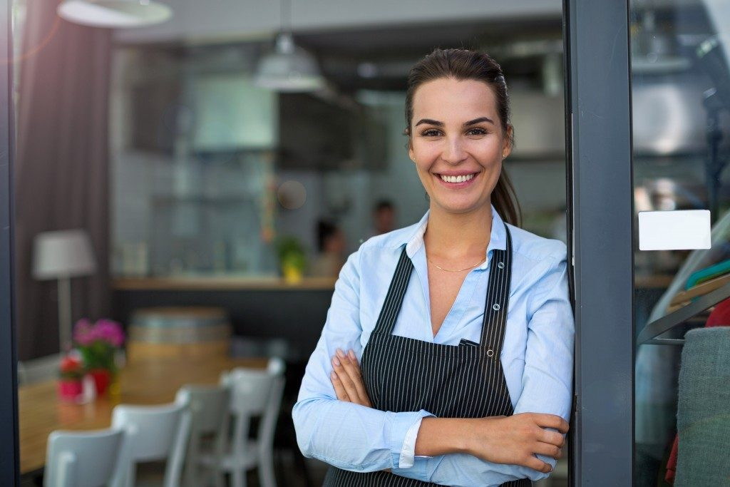 woman standing beside the door of her restaurant