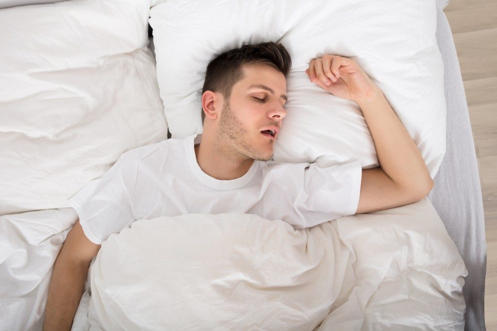 man sleeping soundly under comforter