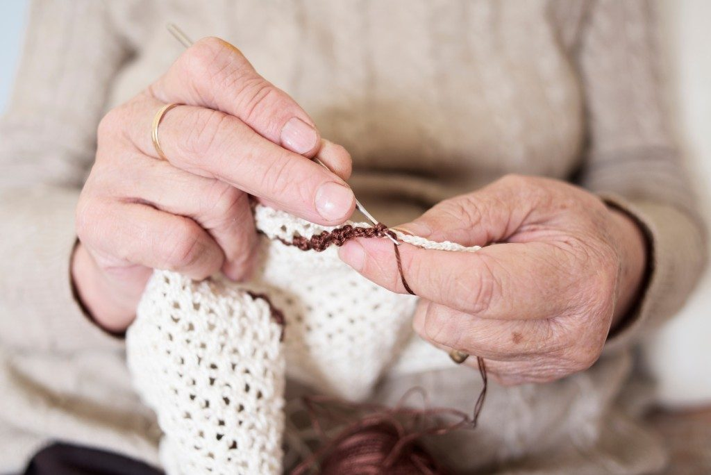 hands of an old person knitting