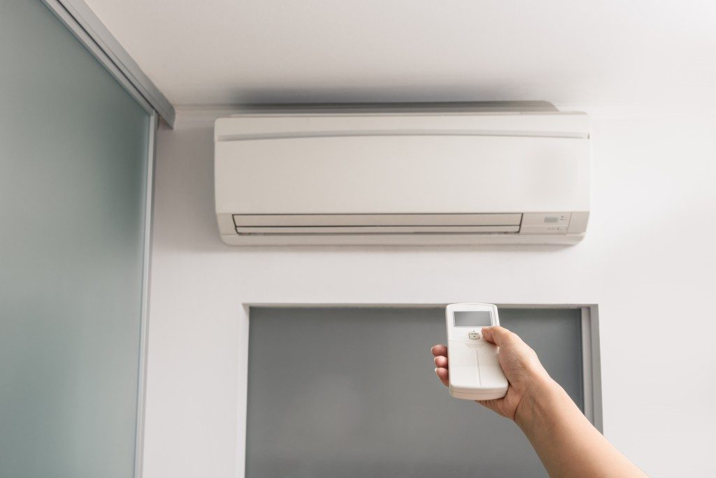 hand with remote control directed to the air conditioner