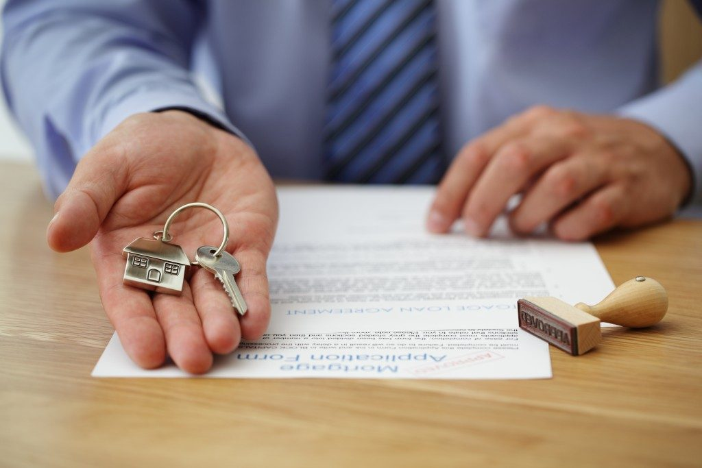 broker handing keys and approved application