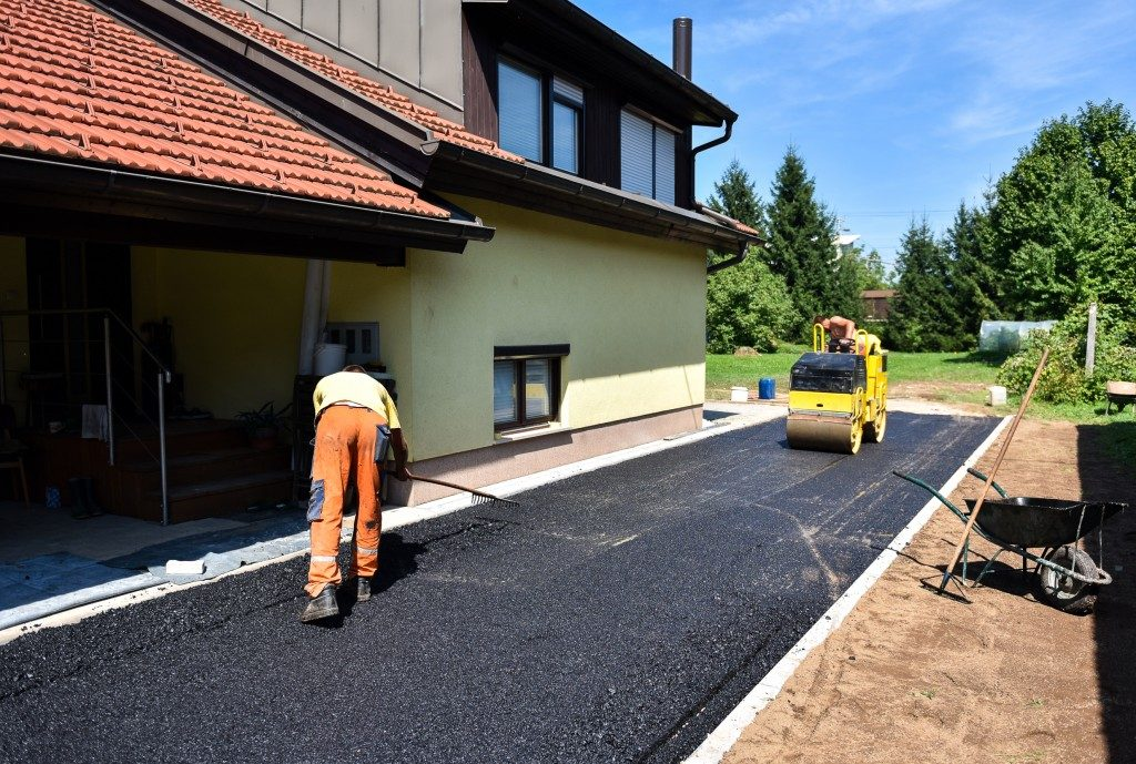 Team of Workers making and constructing asphalt road construction with steamroller.