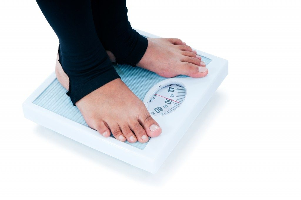 Close-up of a female feet standing on weighing scale.