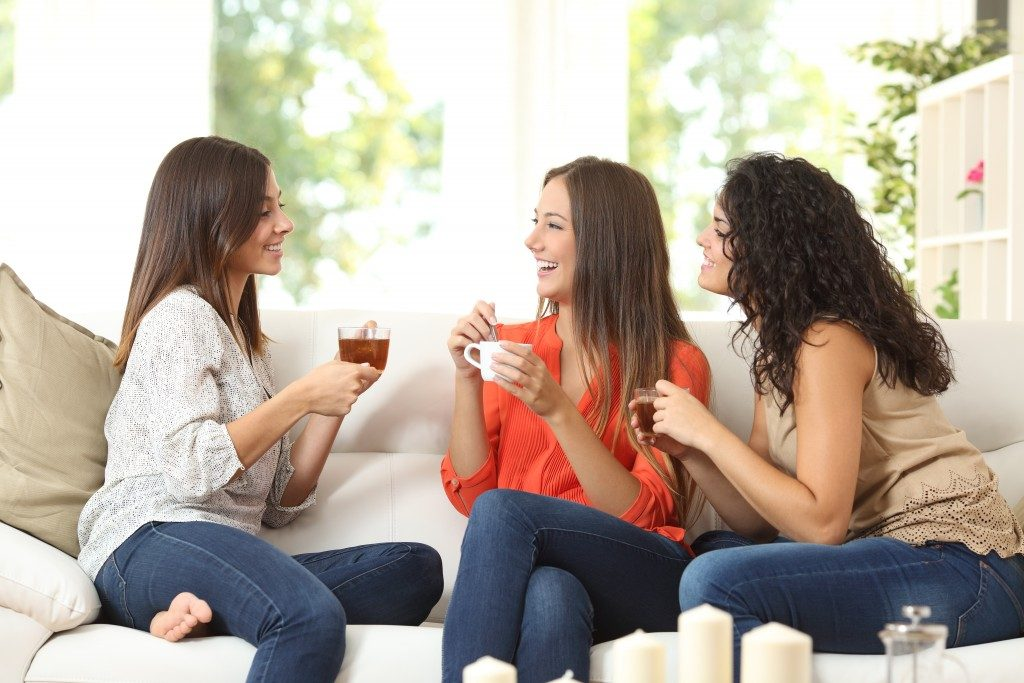 group of women friends having tea in the living room
