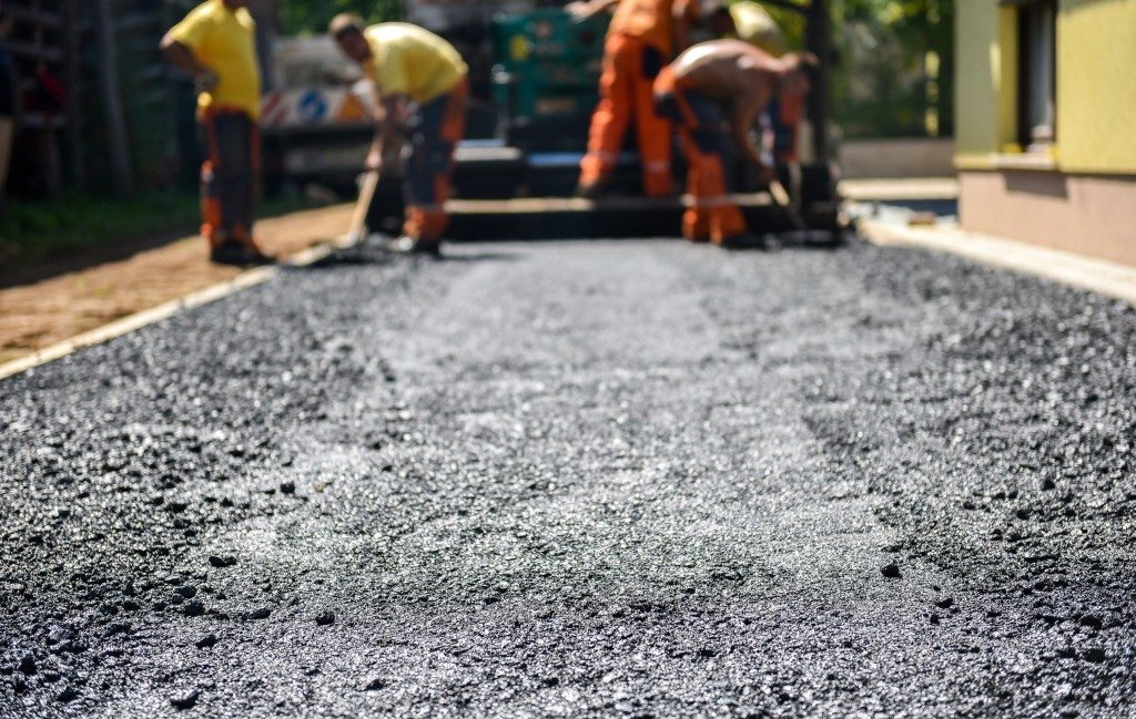 Team of Workers making and constructing asphalt road construction with finisher.