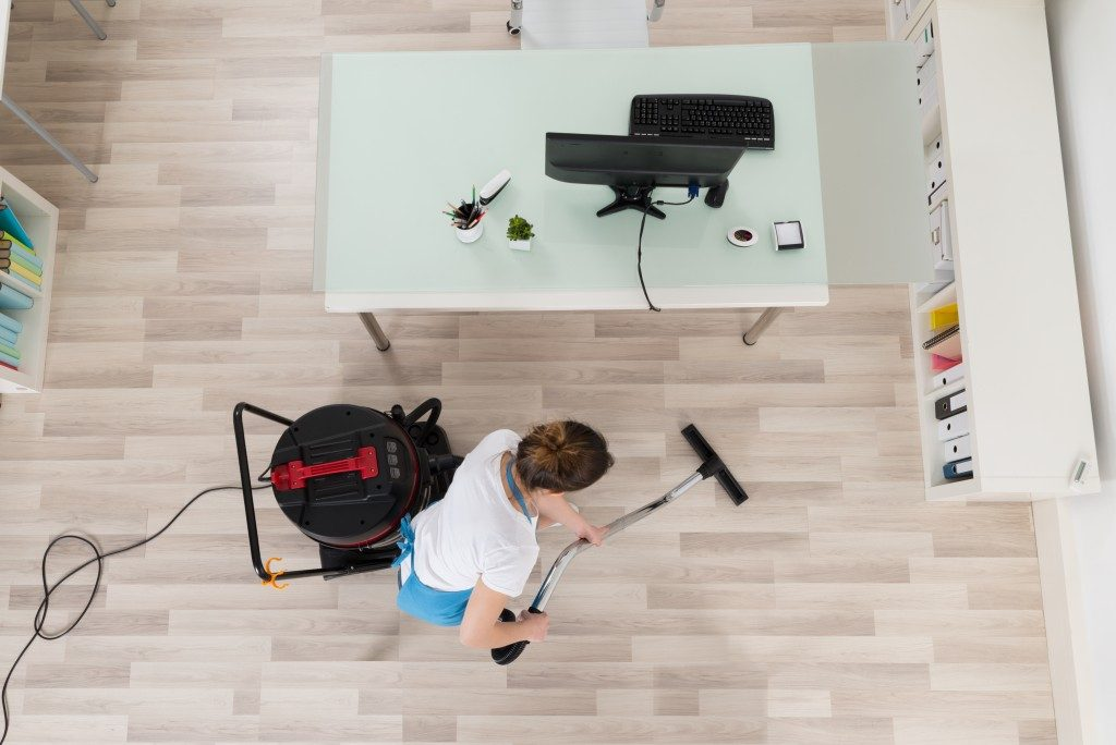 top view of a person vacuuming the floor