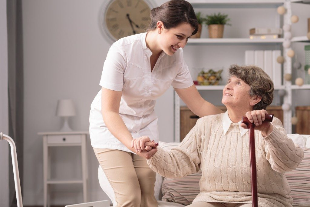 caregiver assisting an old woman to stand up