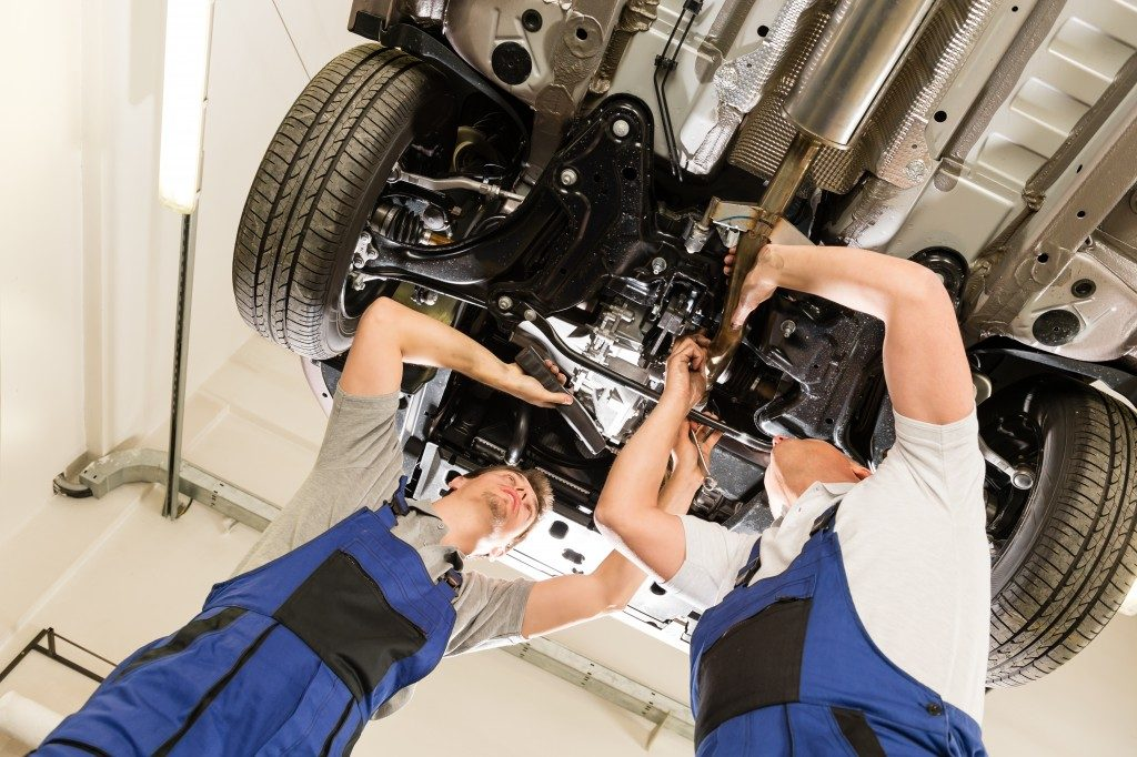 two mechanics checking the engine of a car