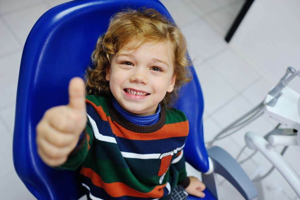 smiling kid sitting on the dental chair