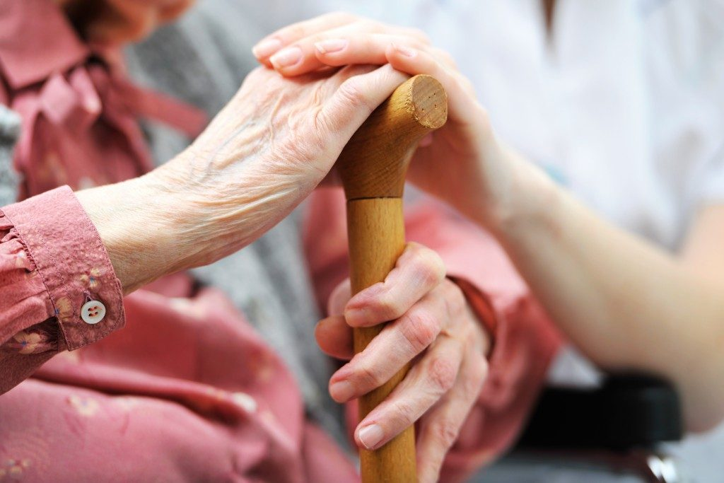 caregiver holding an old woman's hand