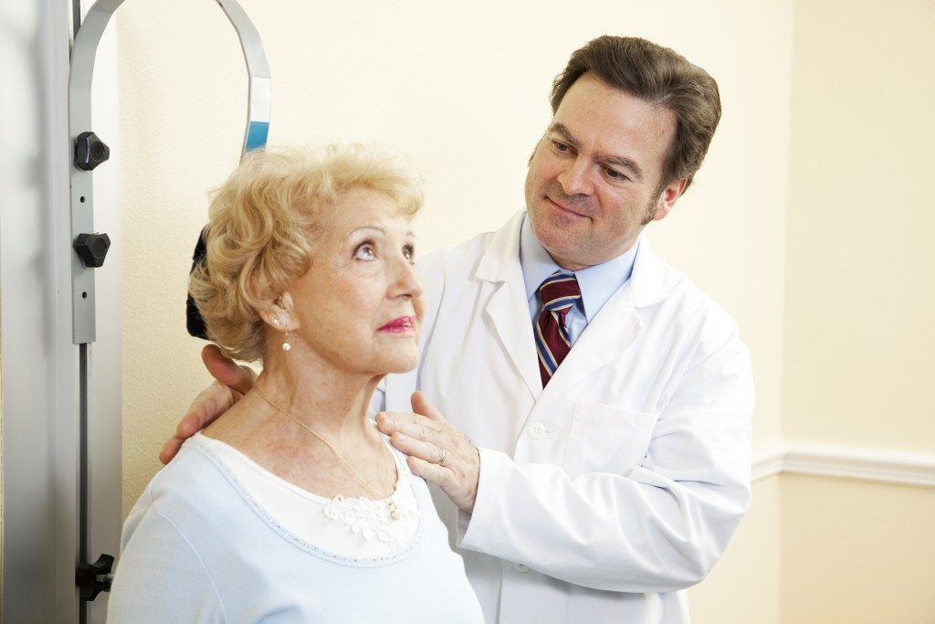 chiropractor treating an elderly woman