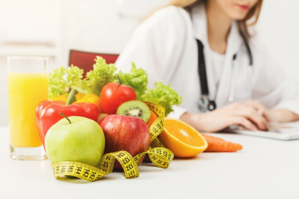 Doctor with fruits and veggies on the table, recommending diet