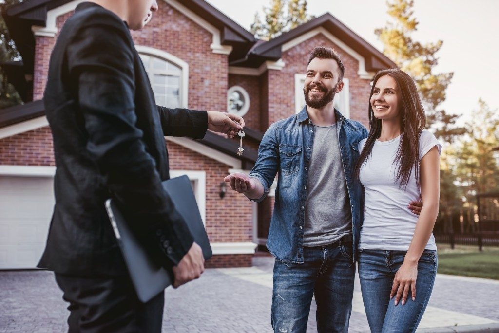 Realtor handing keys to new homeowners