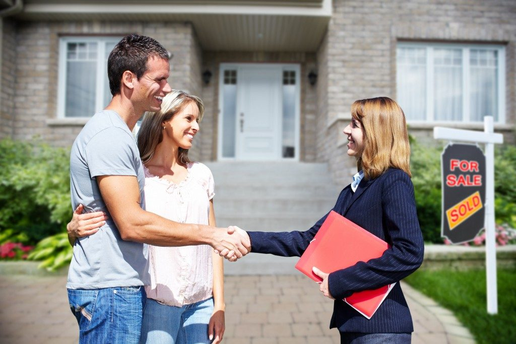 Realtor shaking hands of new homeowners