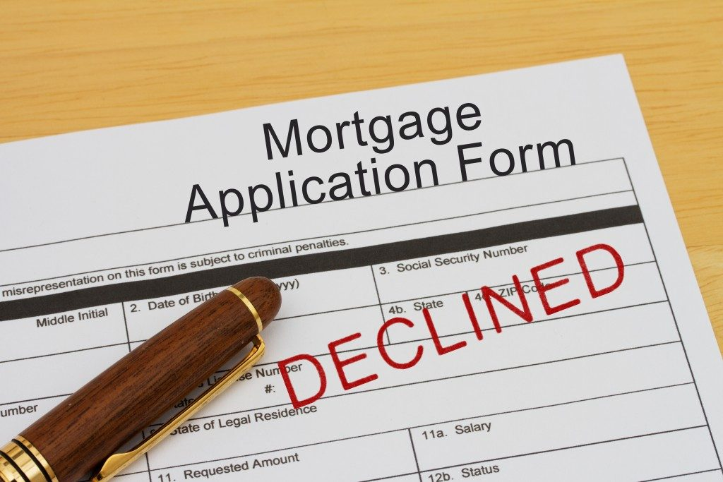 Mortgage Application Form with declined stamp and a pen on a wooden desk