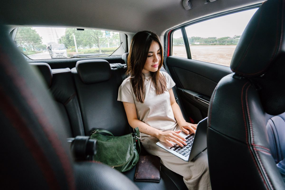 woman working on laptop inside a car