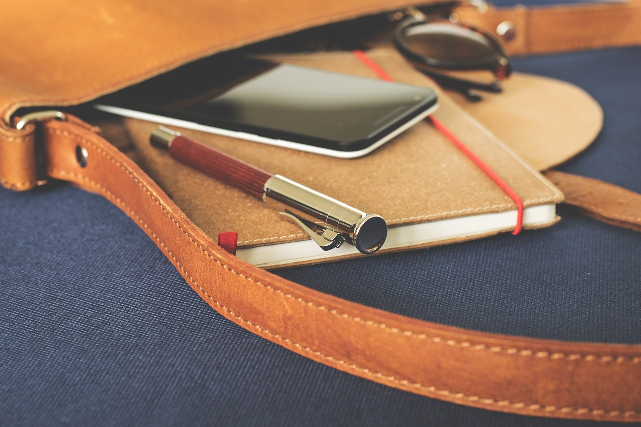 leather bag with sunglasses, phone, notebook and a pen inside.
