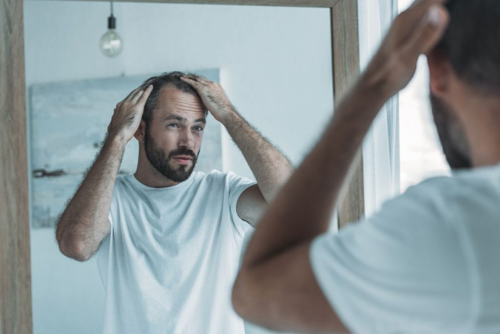 man touching his hair looking in front of the mirror