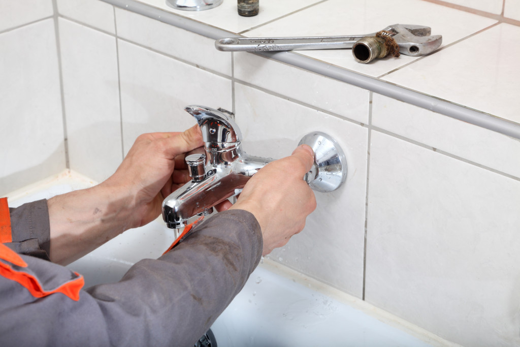 man installing a faucet